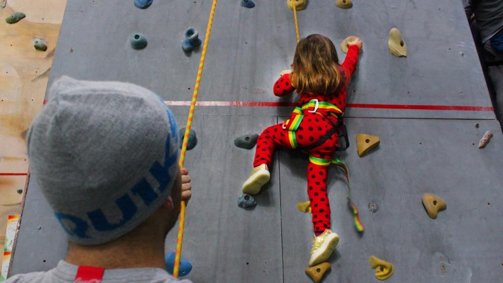 pai dando segurança para filha na escalada